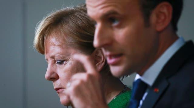 Purtret da Merkel ed davantvart Macron.