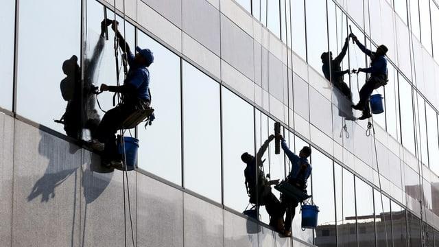 Drei Fensterputzer arbeiten vom Flachdach hängend an einem Haus mit Glasfassade