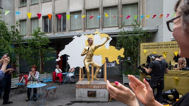 Ein golden gelkeiderter Mann steht vor einer Schweizerkarte.