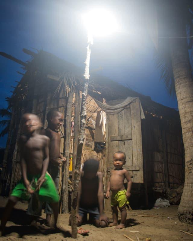 Schwarze Kinder vor einer Hütte, vor der ein Licht brennt.