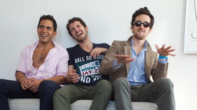 Drei junge Männer sitzen lachend auf einer Couch