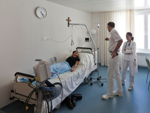 Liegende Patientin hört sich einen Arzt und eine Ärztin bei der Visite an.