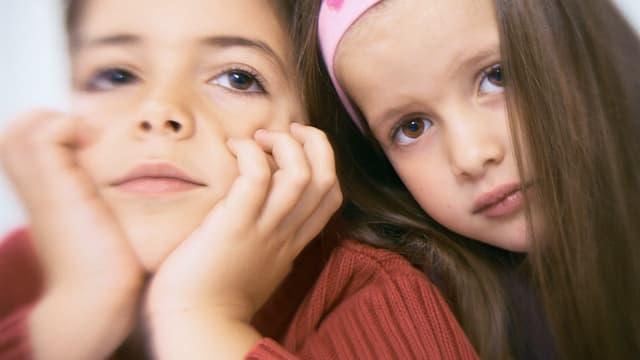 Zwei Kinder mit gelangweiltem Gesichtsausdruck