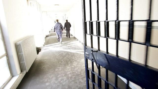 Offene Gittertüre im Rebibbia-Gefängnis in Rom, den Gang entlang gehen drei Männer (von hinten).