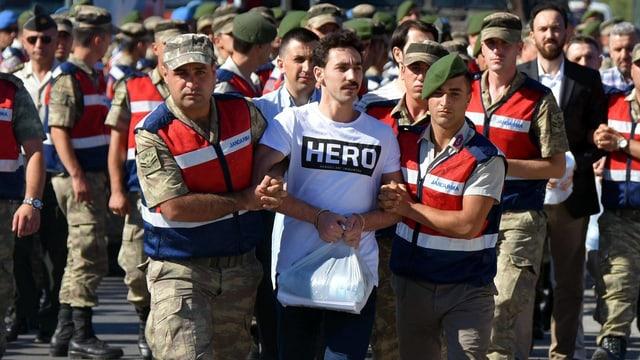 Ein Mann wird von Dutzenden Sicherheitskräften abgeführt, er trägt ein Hero-Shirt.