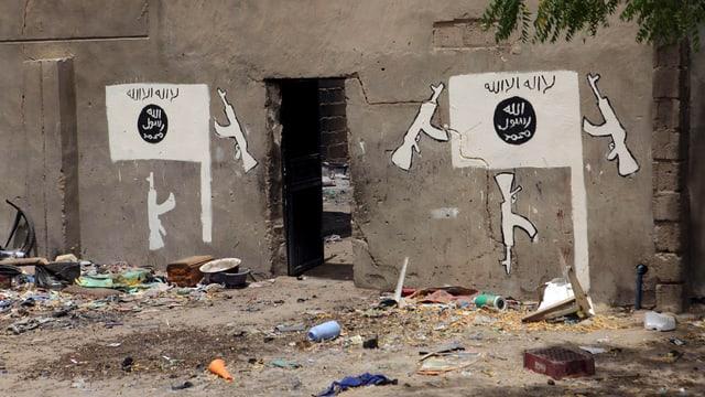 Aufnahme eine Mauer. Links und rechts einer Öffnung ist das Zeichen von Boko Haram aufgemalt.