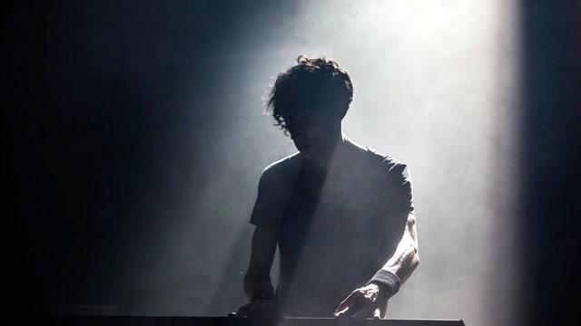 Mann steht im dunkeln an einem Keyboard.