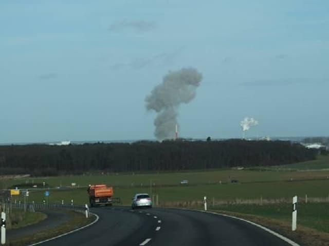 Eine Strasse, dahinter am Horizont steigt Rauch auf.