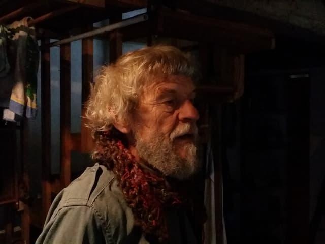 Ulrico Stamani trägt graues langes Haar mit Locken und einen grauen Bart.