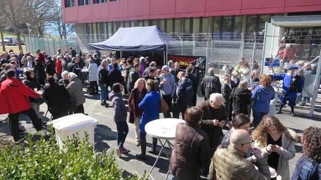 Menschen stehen in kleinen Gruppen vor dem Bundesasylzentrum