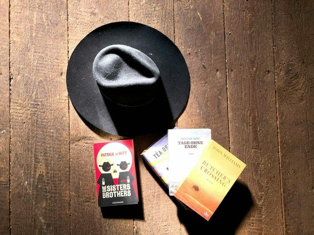 Cowboy-Hut und Western-Bücher auf einem dunklen Dielenboden.