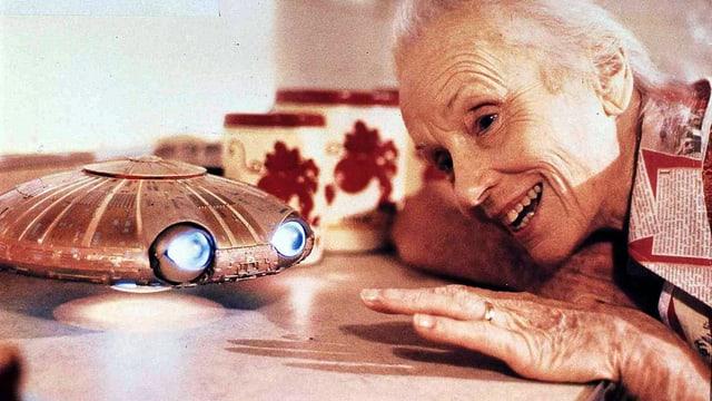 Eine alte Frau schaut mir fröhlichem Gesicht ein kleines Ufo an, das zwei leuchtende blaue Augen hat.