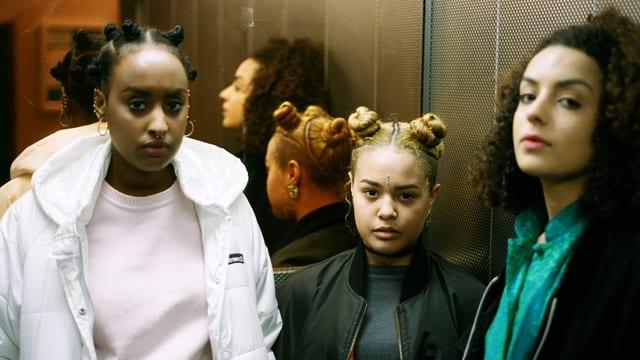 Drei junge Frauen stehen in einem Lift.