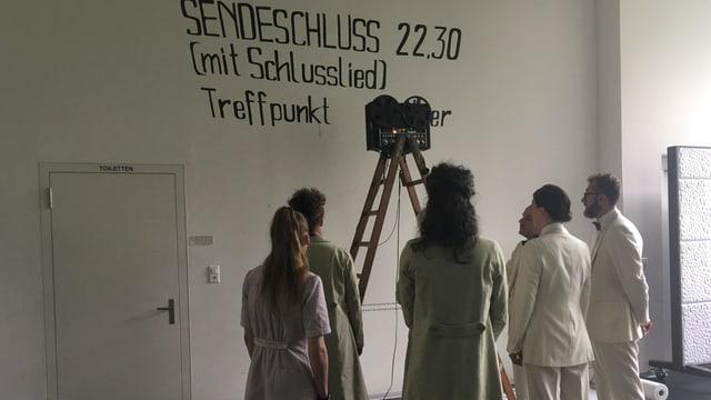 """Schauspieler vor einer Wand auf der """"Sendeschluss"""" geschrieben steht."""