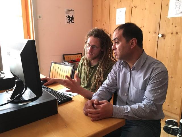 Zwei Männer sitzen vor einem Monitor