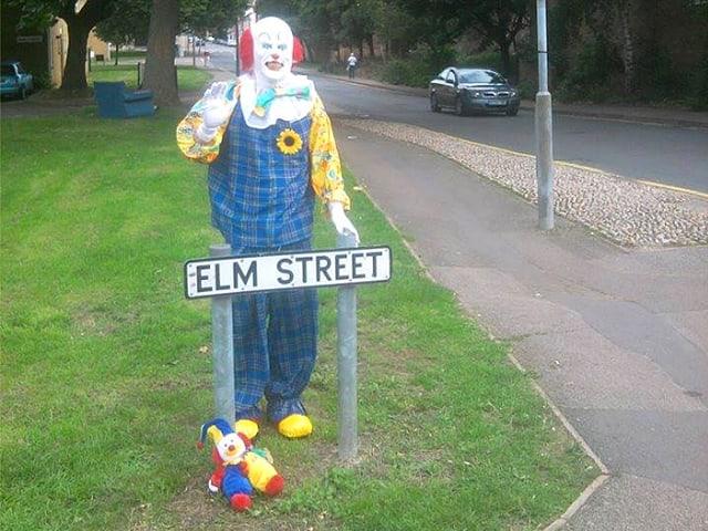 Clown hinter Strassenschild stehend