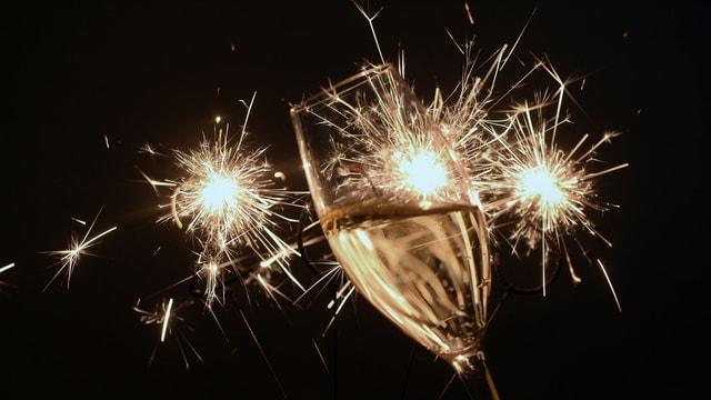 Auf dem Bild ist ein Sektglas zu sehen, im Hintergrund Feuerwerk