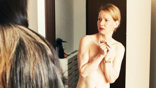 Frau ohne Kleider verschränkt ihre Arme vor ihrem Oberkörper.