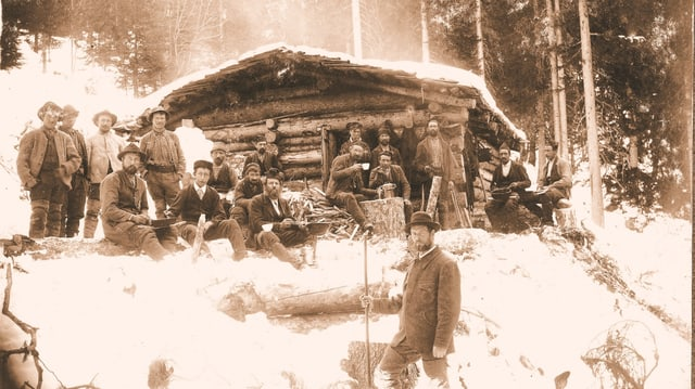 Ina veglia fotografia che mussa lavurers forestals, l'enviern, avant ina tegia da lain.
