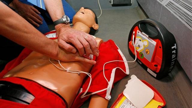Ein Mann verabreicht einer Puppe eine Herzmassage; daneben steht ein Defibrillator.