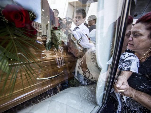 Frau lehnt Gesicht an eine Glasscheibe hinter der der Sarg steht.