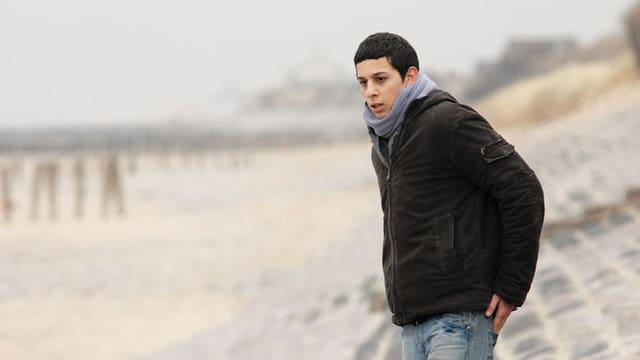 Ein junger Mann steht am Strand.