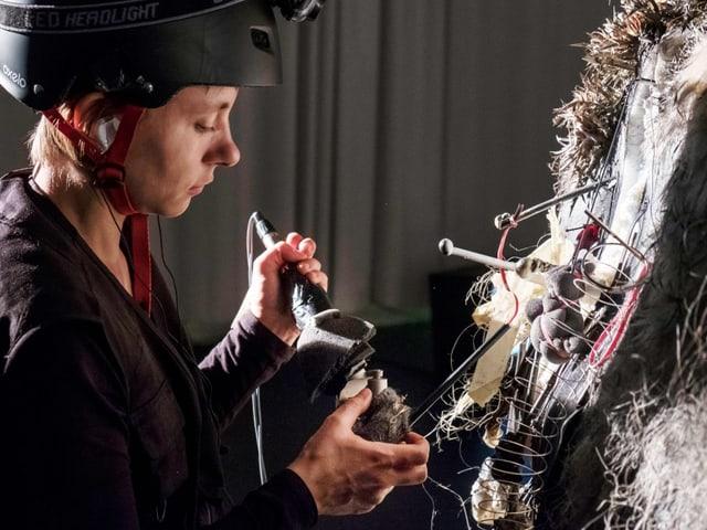 Eine Frau mit Helm vor einer verkablenten Fläche aus unterschiedlichen Materialen. Sie hält ein Gerät daran.
