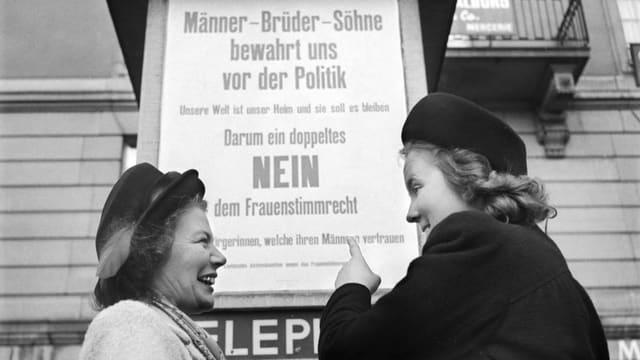 "Duos dunnas il 1950 davant in placat cun l'inscripziun ""Männer - Brüder - Söhne, bewahrt uns vor der Politik. Nein zum Fraunestimmrecht"""