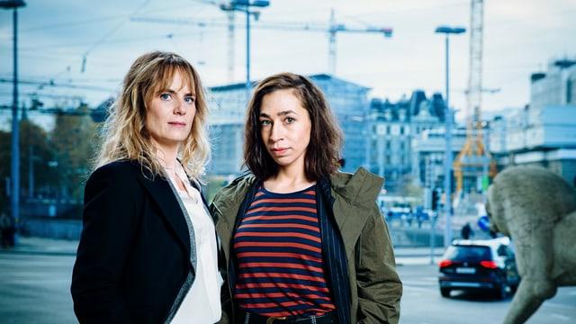 Zwei Frauen stehen vor einer Stadtkulisse und schauen ernst.