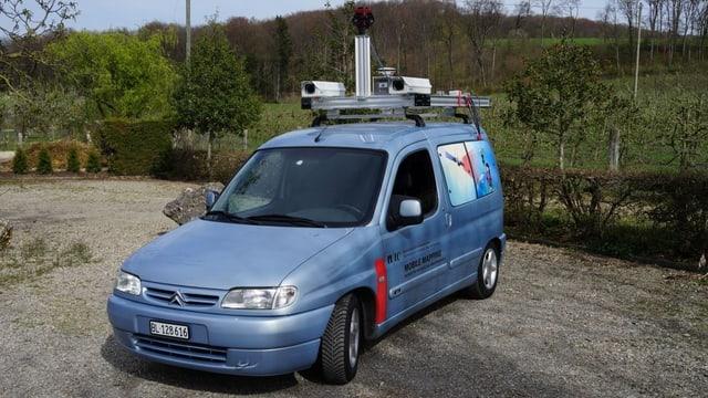 Blaues Kombi-Auto mit verschiedenen Kareas auf dem Dach-