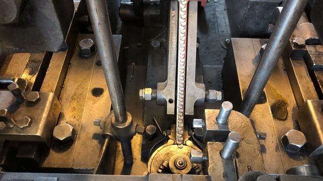 Nägel laufen in einer Maschine auf ein Verteilmechanismus zu.