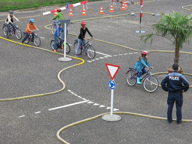 Mehrere Kinder fahren im Kreisverkehr.
