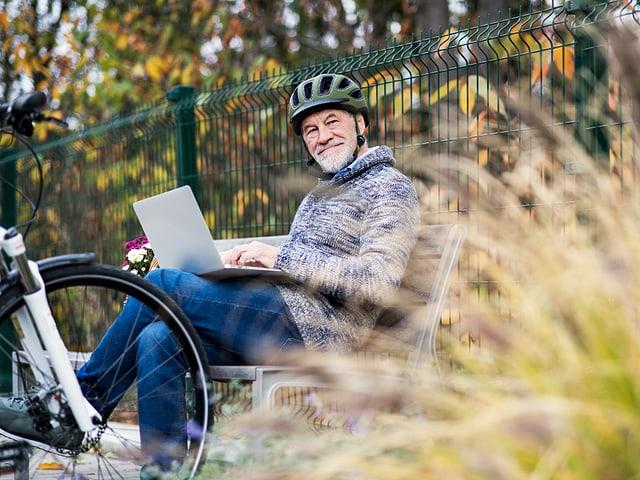 Mann mit E-Bike macht Rast auf einer Parkbank und studiert Reiseroute.