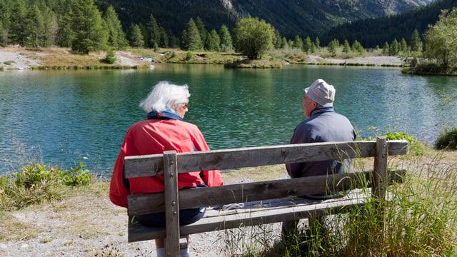 Eine älteres Paar sitzt auf einer Bank an einem Bergsee.