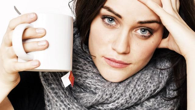 Junge Frau hat den Kopf aufgestützt und schaut direkt in die Kamera, in der Hand eine grosse Teetasse.