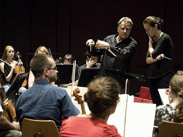 Der Dirigent umbegen von Musikerinnen und Musikern an einer Probe.