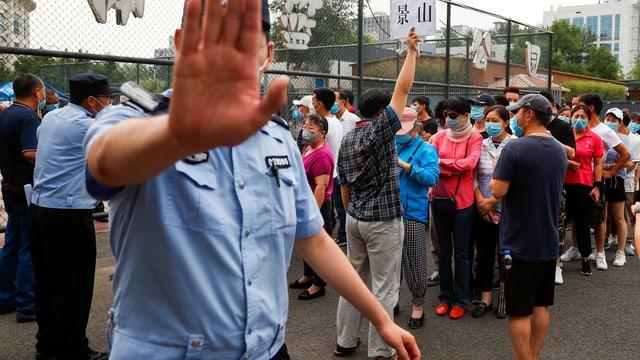 Warteschlange, Menschen mit Gesichtsschutz, ein Polizist im Vordergrund.