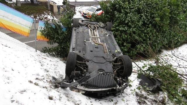 Ein Auto liegt auf dem Dach im Schnee