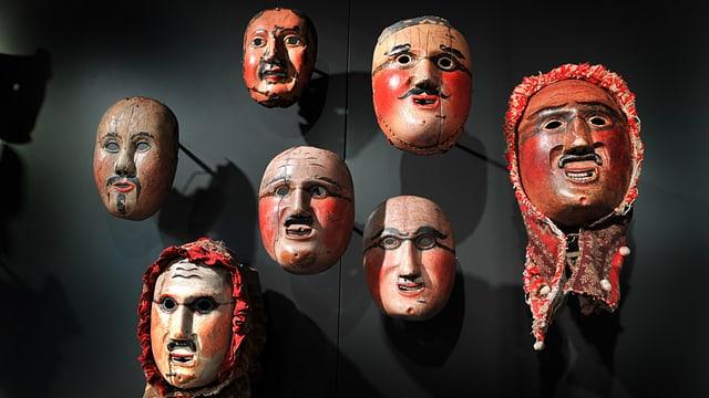 An einer schwarzen Wand hängen sieben männliche Masken.