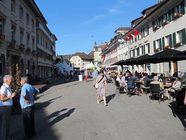 Eine Person läuft durchd ie Gasse, daneben diskutieren zwei ältere Leute miteinander. Rechts im Bild stehen mehrere Tische und Stühle, darin sitzen Menschen und diskutieren.