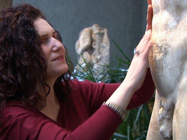 Pina Dolce tastet eine Skulptur in einem Museum mit den Händen ab.