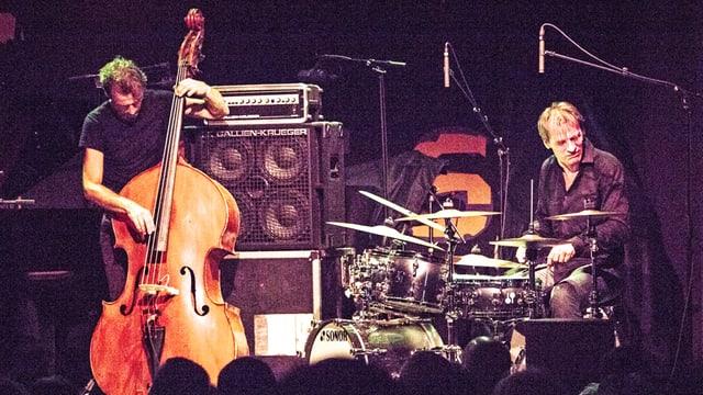 Ein Bassist und ein Drummer auf der Bühne.