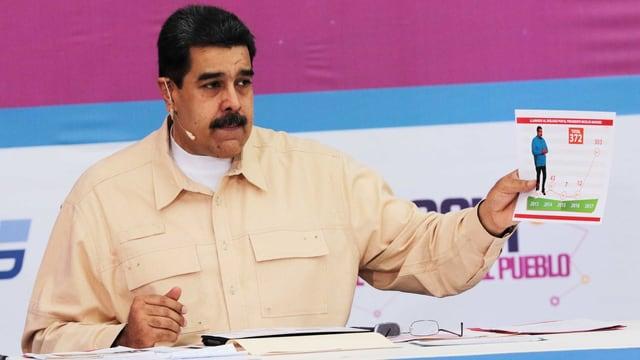 Maduro mit Blatt in der Hand