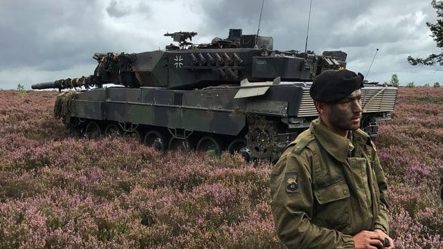 Ein Soldate steht vor einem Panzer