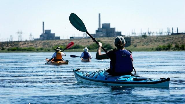Drei Leute paddeln in Kayaks auf einem Fluss.