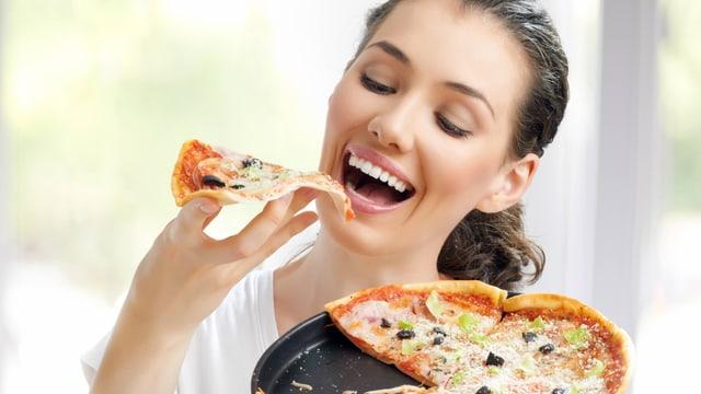 Eine junge Frau hält eine Pizza in der einen und ein Pizzastück in der anderen Hand, in das sie gleich hineinbeisst..
