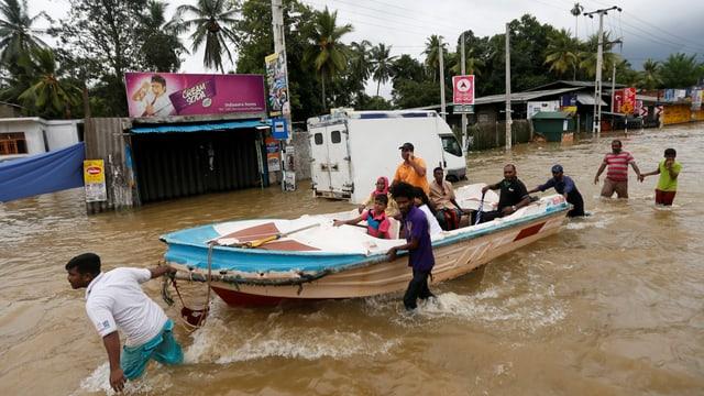 Menschen zeihen ein Ruderboot durch eine überschwemmte Strasse in einem Dorf