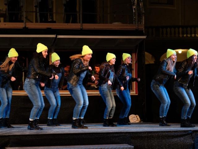 Junge Frauen tanzen auf eine Bühne.