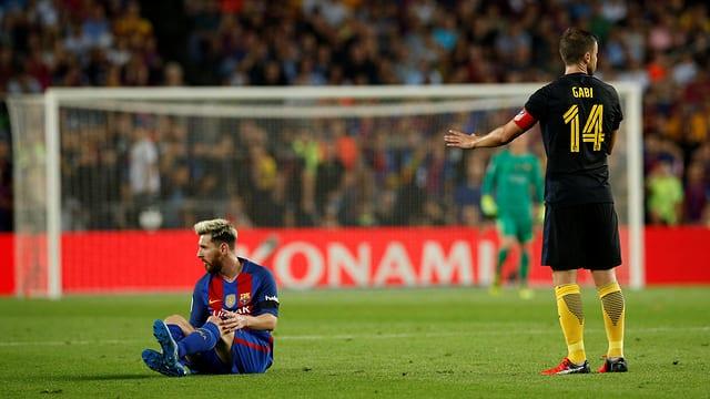 Lionel Messi sitzt am Boden.