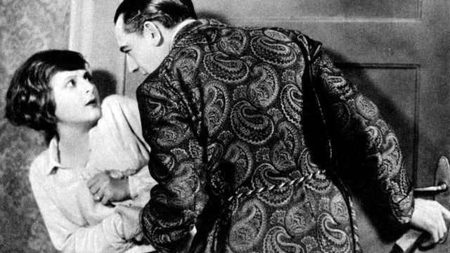 Ein Mann beugt sich über eine junge eingeschüchterte Frau und schliesst versteckt die Türe ab.